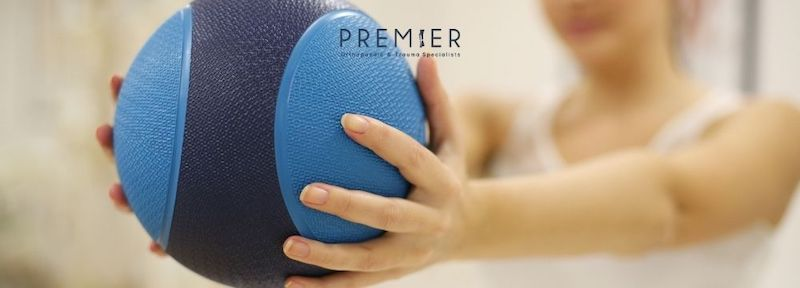 Woman at physical therapy with medicine ball regaining strength and function after an orthopedic injury and treatment at Premier Orthopaedic & Trauma Specialists