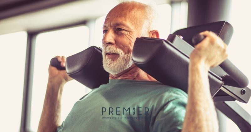 Older man exercises using weight bearing activities to improve strength and bone heath as instructed by his orthopedic surgeon. Premier Ortho logo at bottom center.