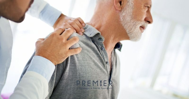 Man with white beard has shoulder pain evaluated by a board certified orthopedic surgeon for bursitis or rotator cuff injury. Premier Ortho logo at bottom center.
